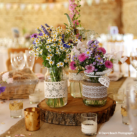 Jam jars filled with spring flowers makes a beautiful wedding centrepiece in the South Barn