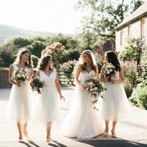 A bride and her bridesmaids all wear white for a wedding at Upwaltham Barns in Sussex