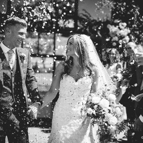 A bride and groom enjoy wedding confetti at Upwaltham Barns