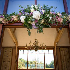 Wedding flowers adorn the doorway to the East Barn at Upwaltham Barns