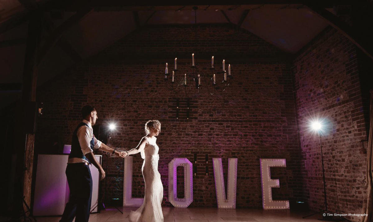 Bride and groom outside of the love sign at Upwaltham Barns - © Tim Simpson Photography