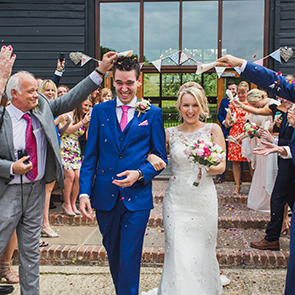 Bride and groom leaving the venue at Upwaltham Barns