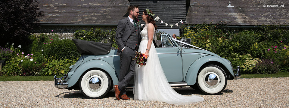 Bride and groom stood infront of a vintage car
