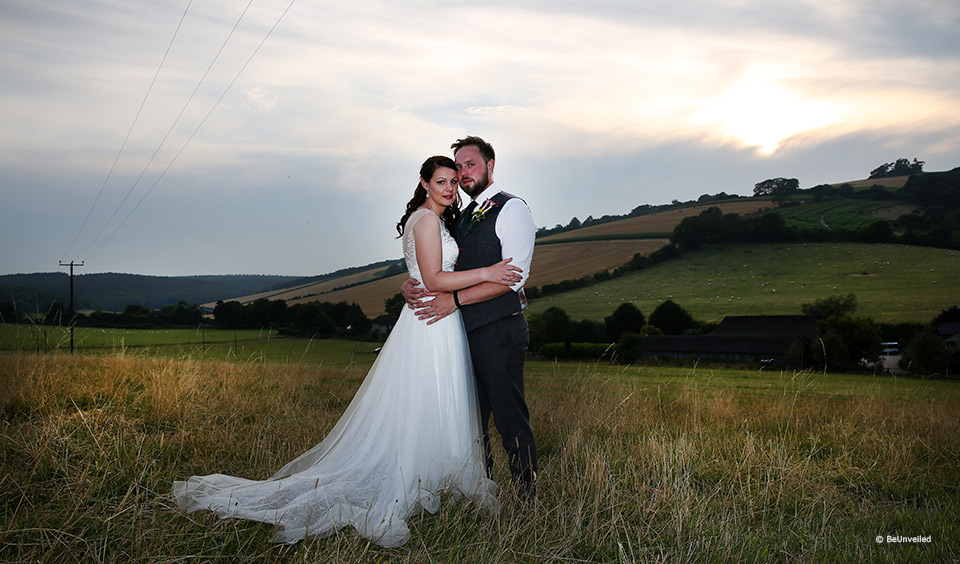 Bride and groom stood in the outdoor space at Upwaltham Barns