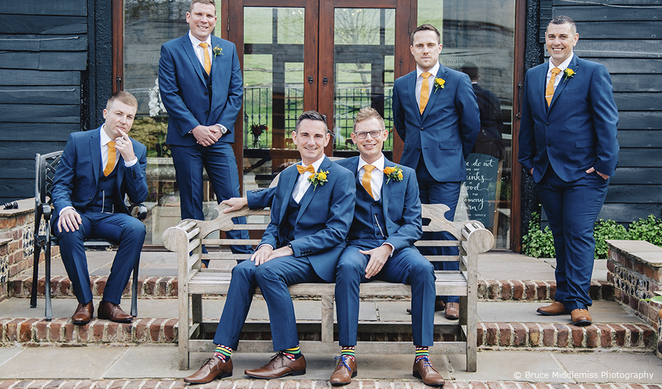 Grooms and groomsmen stood outside of Upwaltham Barns