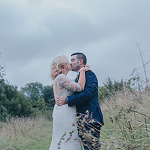 Bride and grooms kiss in the Upwaltham Barns outdoor space