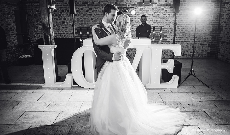 Husband and wife enjoy a romantic first dance in front of giant love letters