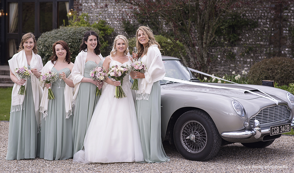 Dressed in sage green the bridesmaids stand with the bride next to a silver Aston Martin DB5 – spring wedding