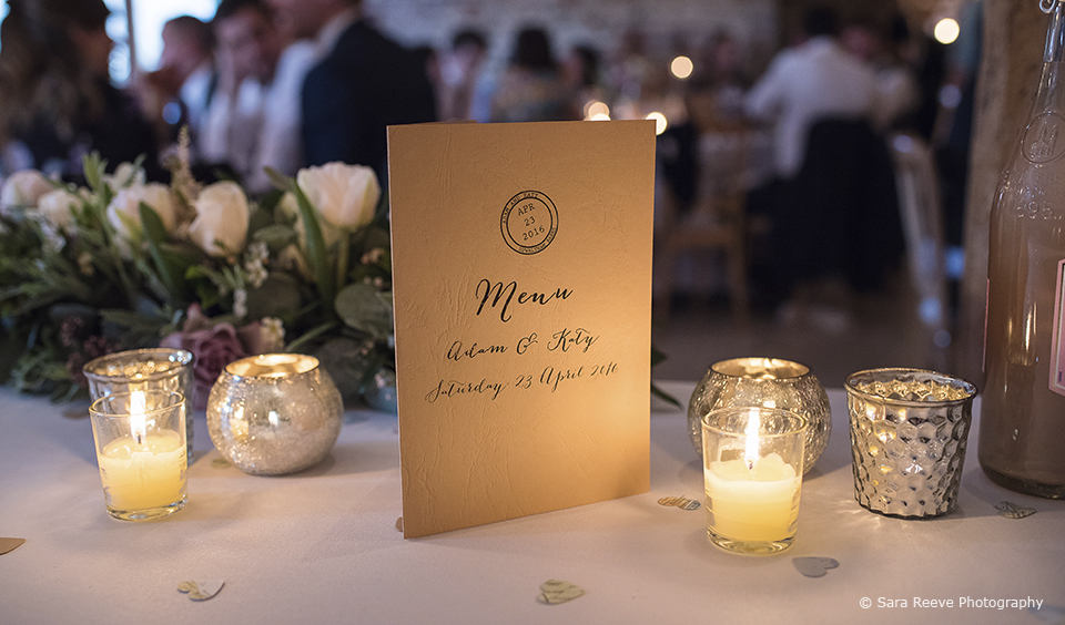 A wedding breakfast menu sits amongst candles and tealights on the tables