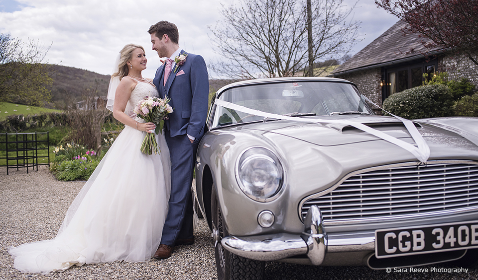 The newlyweds have a special moment next to the Aston Martin DB5 wedding car