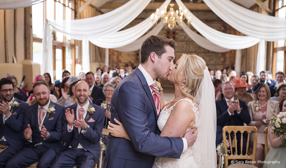 The couple enjoy their first kiss as husband and wife in front of their guests at the wedding ceremony