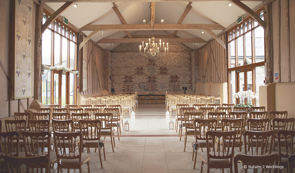 The beautiful East Barn at Upwaltham Barns is set up for the stunning wedding ceremony