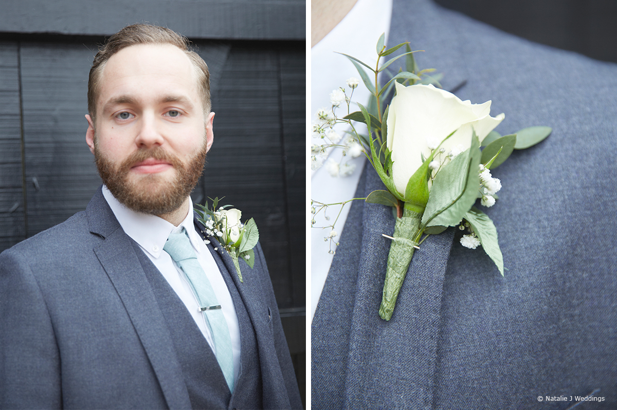 Fit for a spring wedding the groom wears a navy blue suit and pale blue tie with a simple white buttonhole
