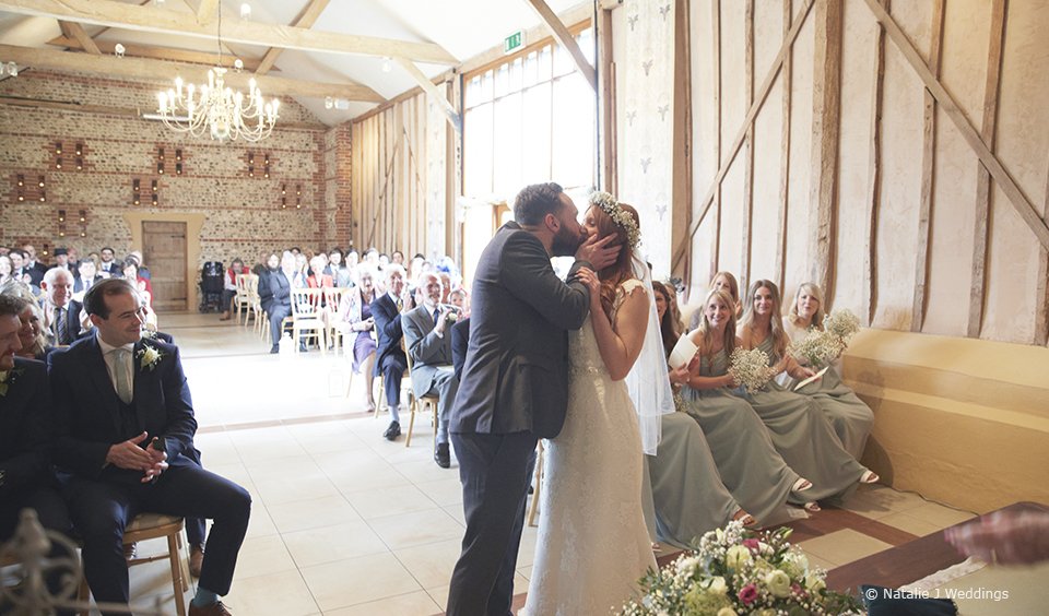 The bride and groom share their first kiss at the wedding ceremony in the East Barn at Upwaltham Barns