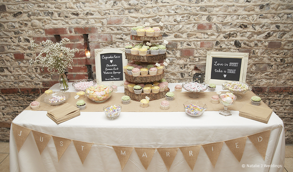 A sweet and cake table is adorned with tasty treats and a tower of wedding cupcakes – wedding ideas