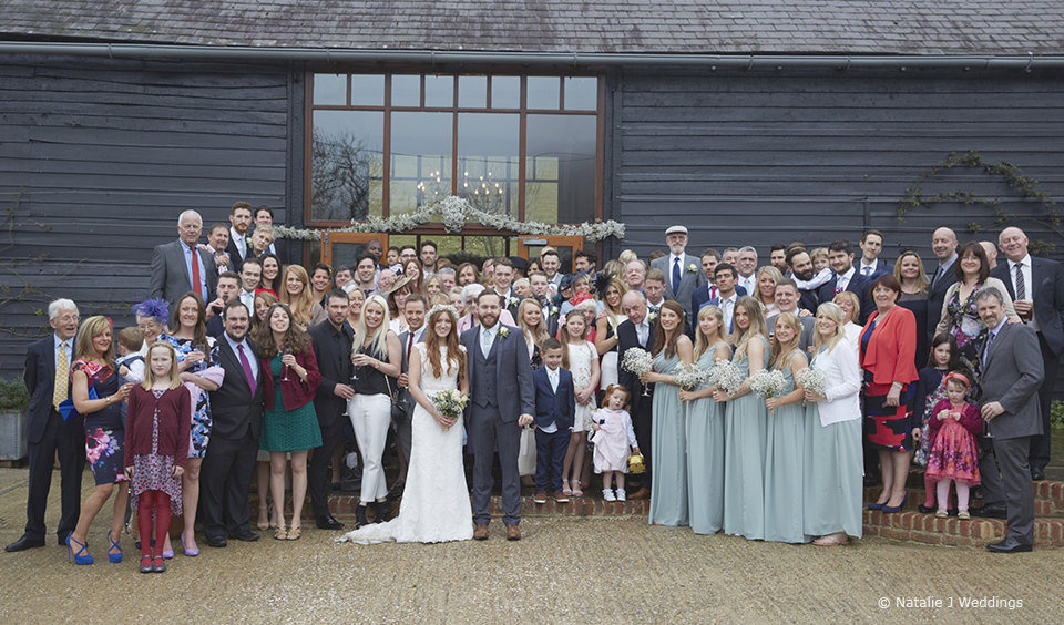 The bride and groom gather with the wedding party for a group photo outside the East barn at Upwaltham Barns