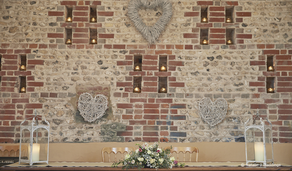 Wedding flowers and candles adorn the East Barn for an elegant wedding ceremony