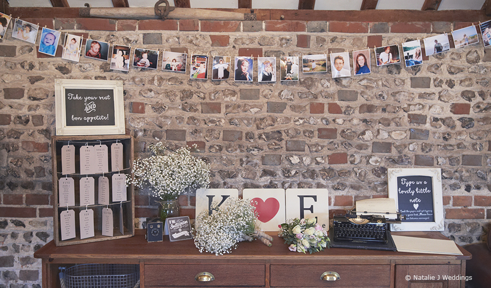 A table adorned with photographs and a typewriter creates an alternative wedding guest book station – wedding ideas