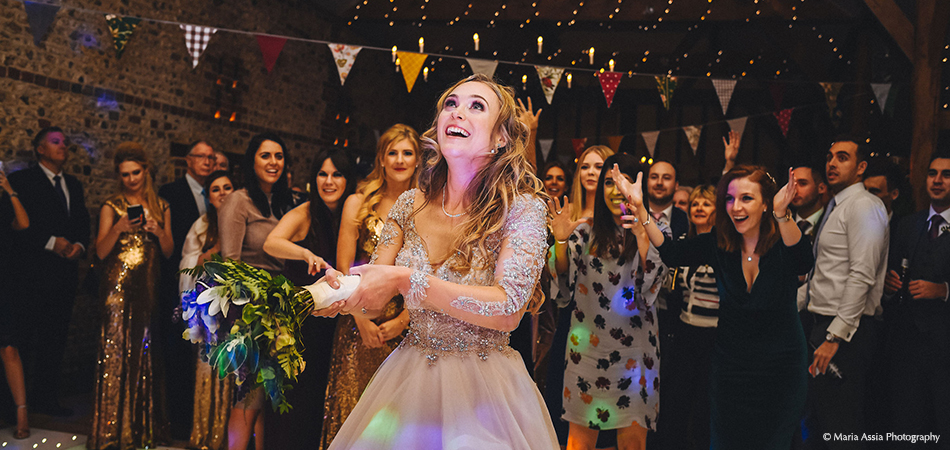 The bride looks to toss her bouquet in the South Barn at Uplwathlam Barns