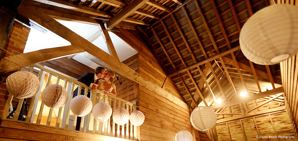 A bride and groom steal a kiss on the balcony in the Jasmine Cottage at Upwaltham Barns