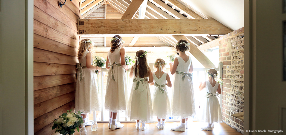A group of bridemaids watch guests arrive for the wedding ceremony from the balcony in the Jasmine Cottage