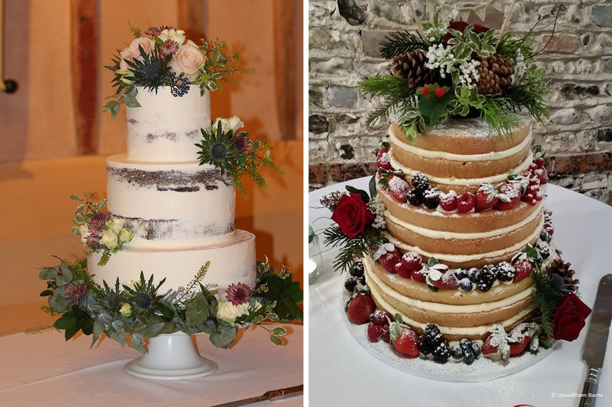 Two wedding cakes covered in roses and acorns