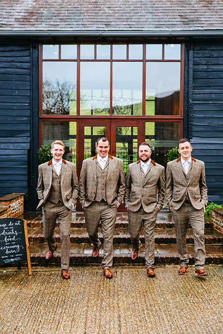 The groom and his groomsmen stand outside Uplwaltham Barns in their brown tweed wedding suits