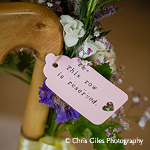 A reserved seating tag within floral decorations adds perfect detail to the wedding ceremony - wedding ideas