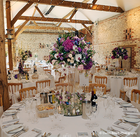 Colourful wedding flowers look great in the South Barn wedding reception venue and are perfect for a summer wedding