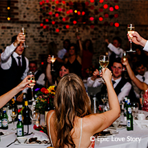 A toast to the bride and groom at their evening wedding reception in the South Barn
