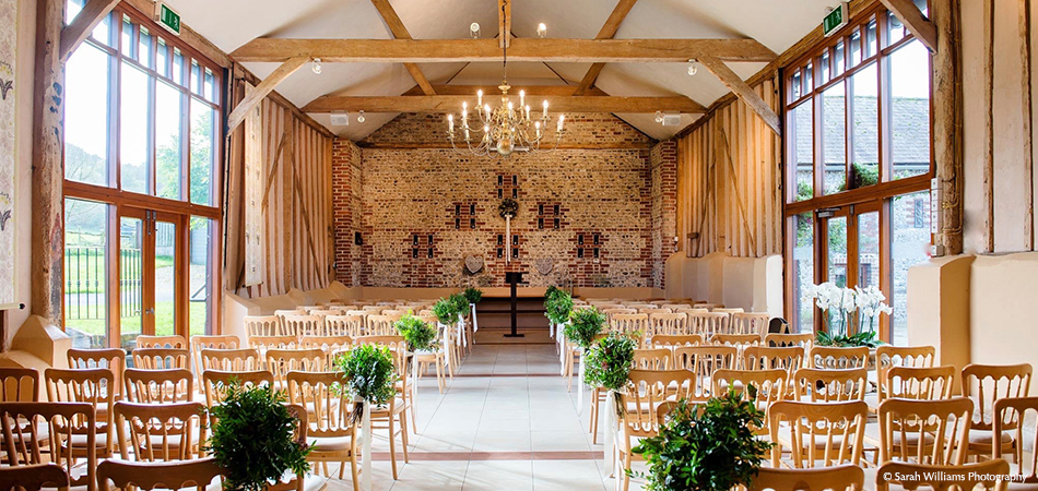 The stunning East Barn is set up for an elegant wedding ceremony at the Sussex wedding venue