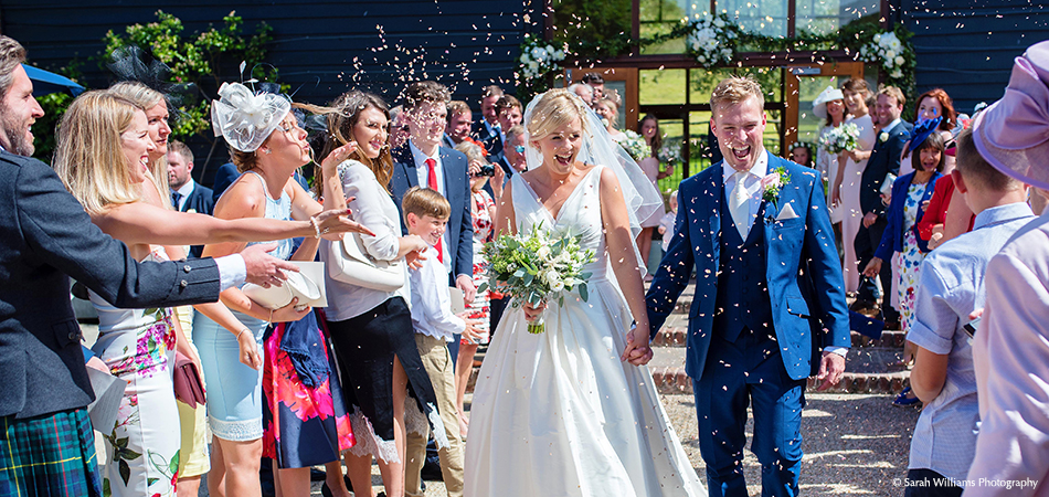 Newlyweds walk amongst their wedding guests as confetti is thrown outside the East barn