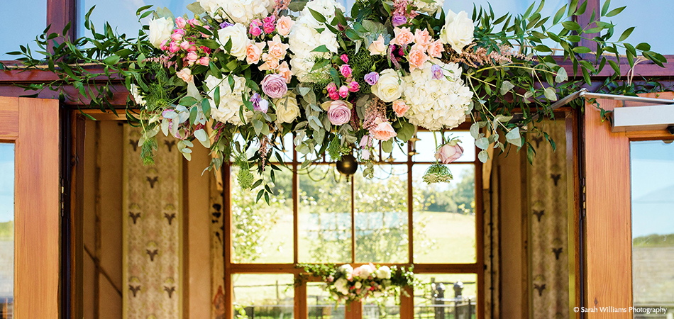 Pink and cream wedding flowers adorn the doorway to the East Barn at Upwaltham Barns