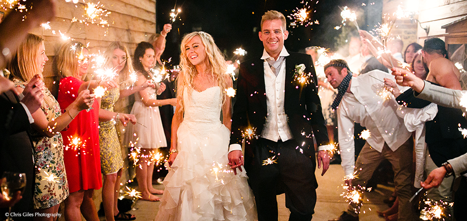 The newlyweds make their way through guests holding wedding sparklers at the end of their wedding day