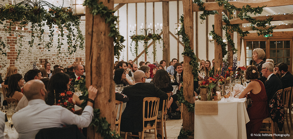 The wedding speeches take place in this stunning barn wedding venue which is adorned with wedding flowers