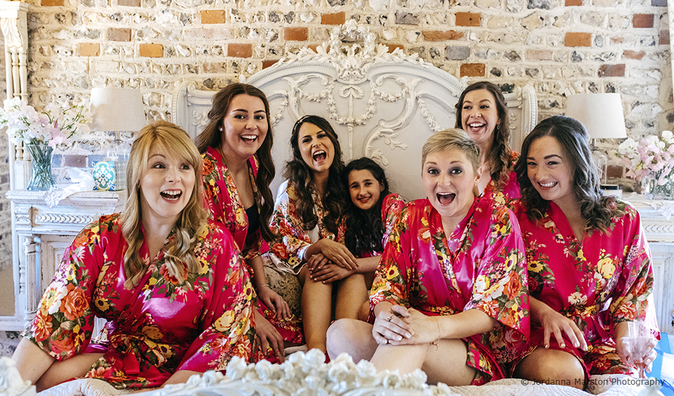 The bride and her bridesmaids have fun before the wedding ceremony at Upwaltham Barns
