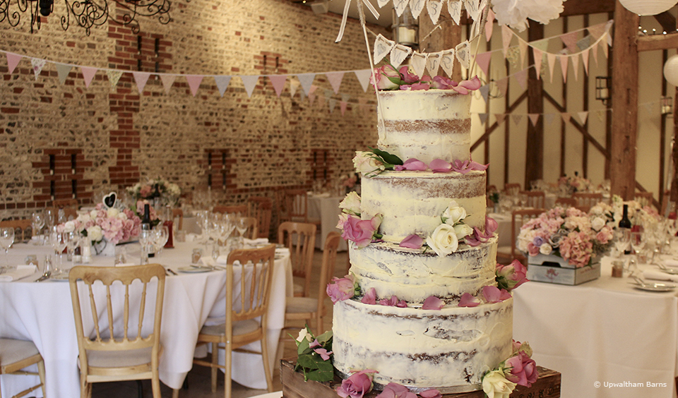 A simple bunting cake topper adds simple detail to a four tiered naked wedding cake at Upwaltham Barns