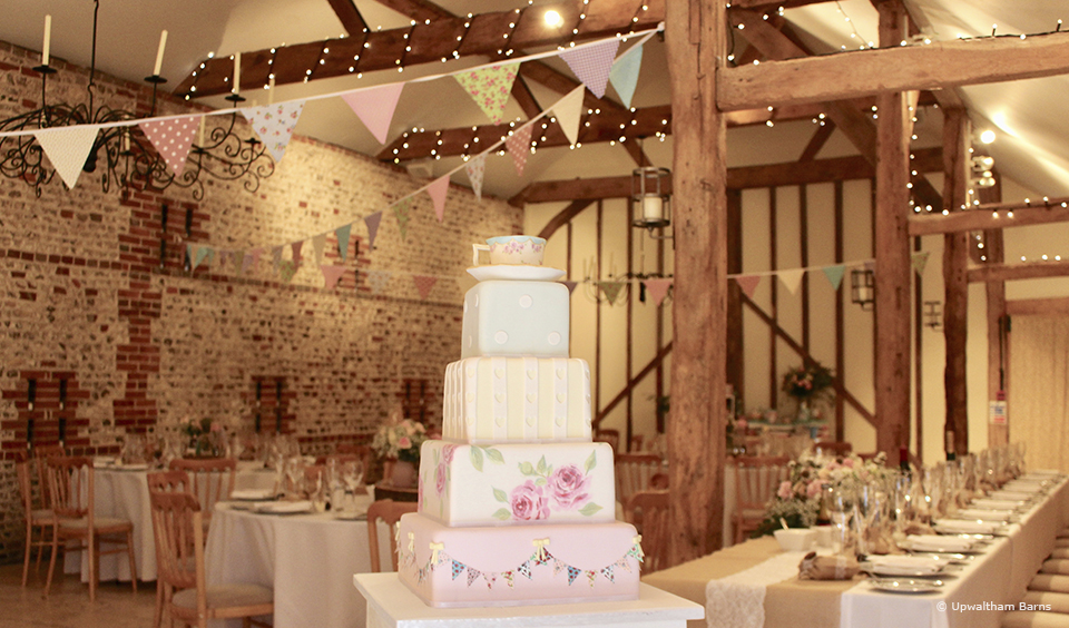 A vintage wedding cake is decorated with bunting to reflect the pastel bunting that decorates the South Barn at Upwaltham Barns