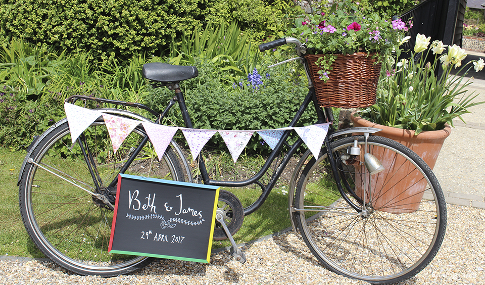 A vintage bicycle is used as a welcome sign and decorated with bunting for a wedding at Upwaltham Barns – wedding ideas