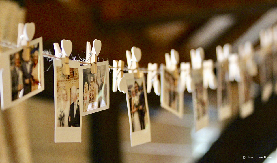 Polaroid photographs are attached to string with heart shaped pegs to create beautiful personalised bunting at Upwaltham Barns