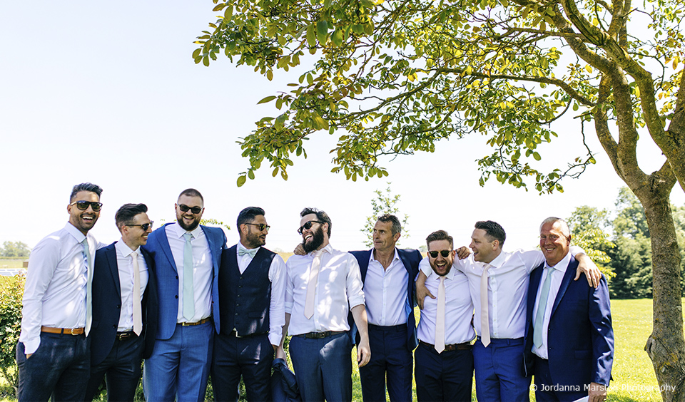 The groomsmen gather and have some fun in the sun before the wedding ceremony at Upwaltham Barns