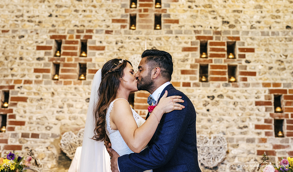The newlyweds share their first kiss as they say I do in The East Barn at Upwaltham Barns