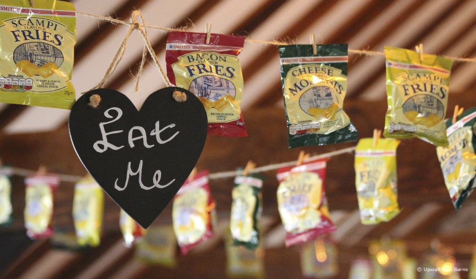 A simple eat me sign encourages guests to tuck in to crisps that have been used as an alternative bunting idea