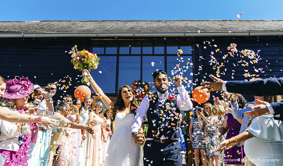 The bride and groom celebrate as their guests throw wedding confetti after their wedding ceremony at Upwaltham Barns