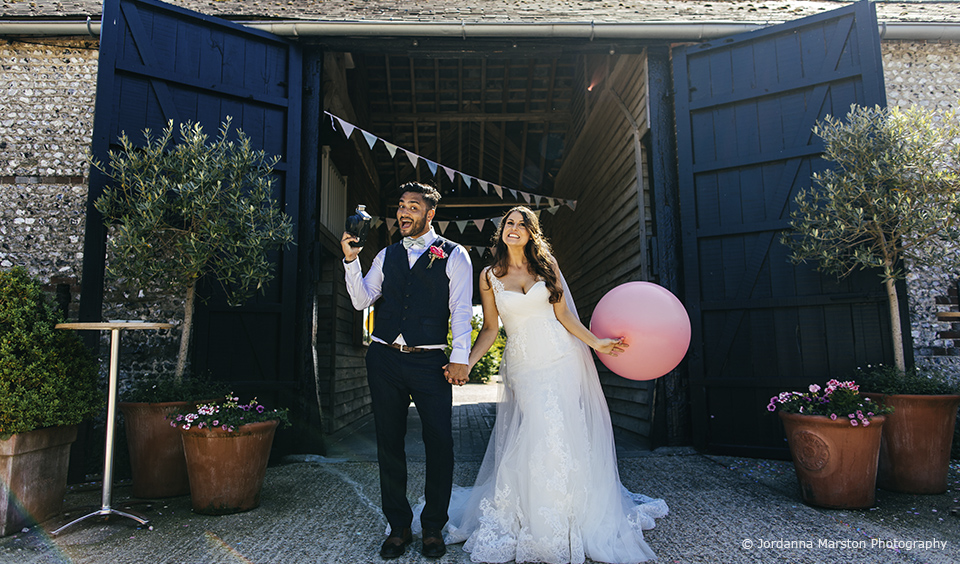 The newlyweds have fun posing for a photo outside the barn wedding venue – wedding ideas