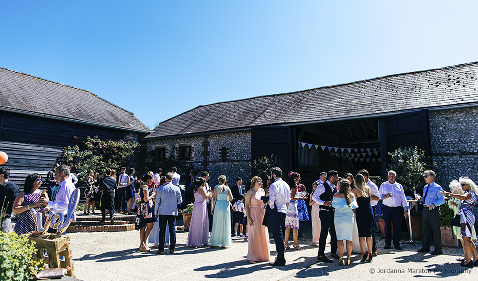 Guests gather in the courtyard at Upwaltham Barns for a beautiful barn wedding