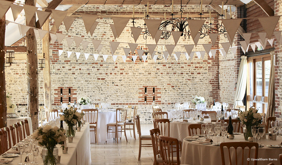 Simple white bunting hangs in the South Barn ready for an elegant wedding reception at Upwaltham Barns
