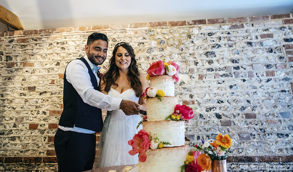 The bride and groom cut their 4 tier wedding cake at Upwaltham Barns wedding venue in West Sussex