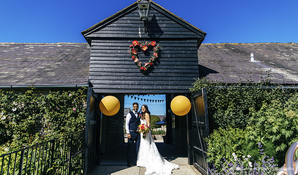 The new husband and wife stand outside the beautiful Upwaltham Barns wedding venue after their stunning summer wedding