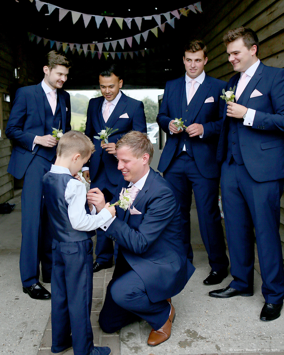 The groom and groomsmen wear navy blue suits as they gather outside Upwaltham Barns wedding venue